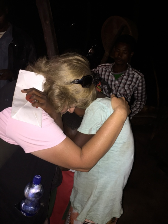 Lori praying with her sponsor child and his family